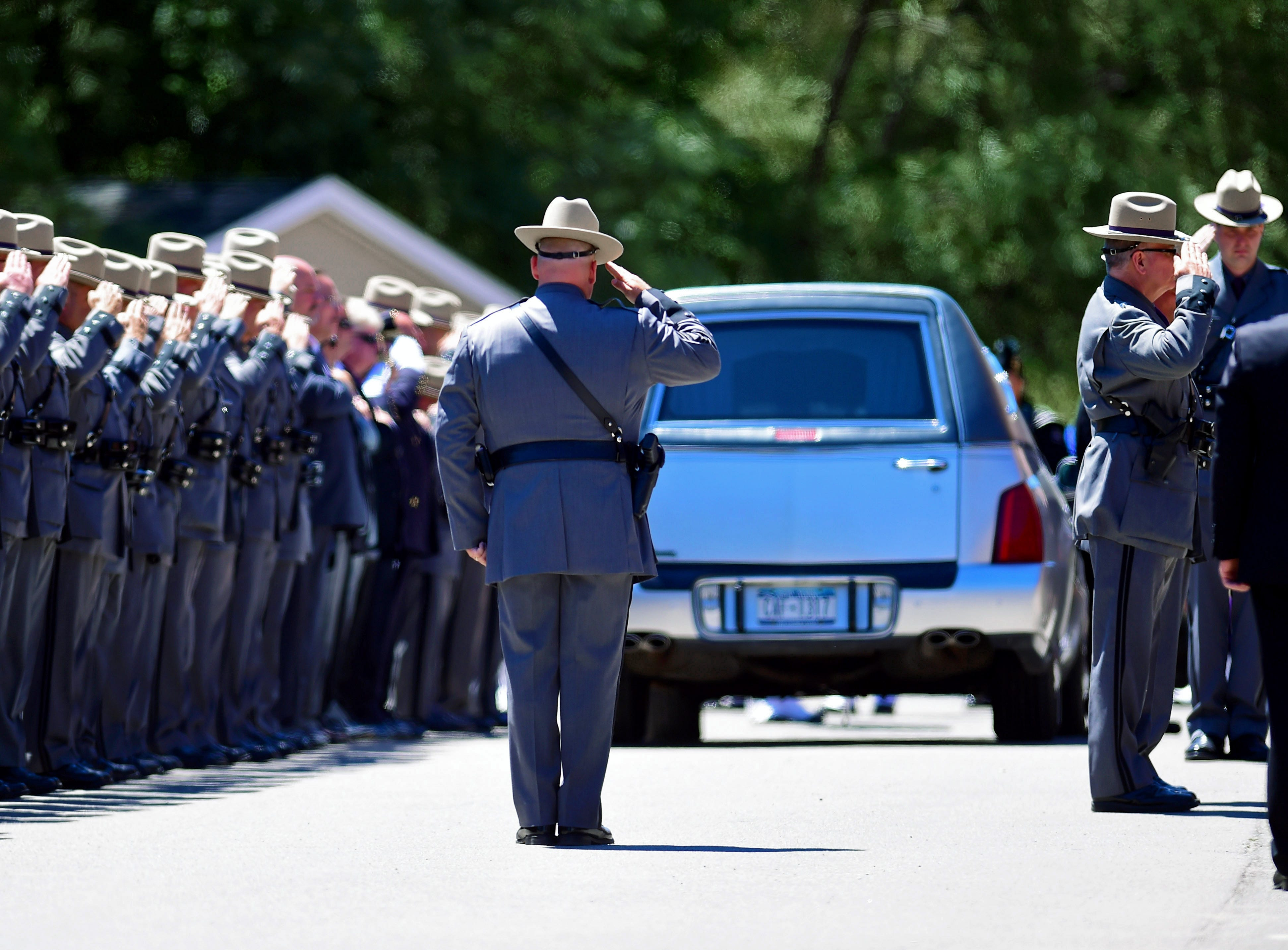 New York State Police Superintendent George P. Beach II salutes as the hearse carrying the remains of Trooper Nicholas F. Clark departs the slain trooper's funeral service at the James A. McLane Physical Education Center, Alfred University, Alfred, NY, on July 8, 2018.
