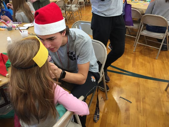 Union-Endicott High School student Christian Abadessa paints the face of an elementary school student at the Key Club's holiday party on Dec. 20.