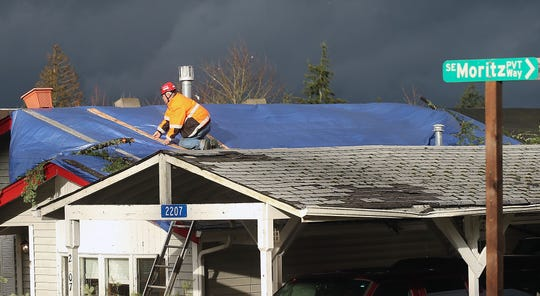 A roof tarp is secured at the corner of Harris and Serenade Way as residents and work crews clean up the aftermath of a Dec. 18 Port Orchard. Those whose homes and businesses were hit by the tornado are in various stages of working with adjusters and insurance companies, and nonprofits are working to find out which residents and business owners are coming up short because of gaps in coverage.