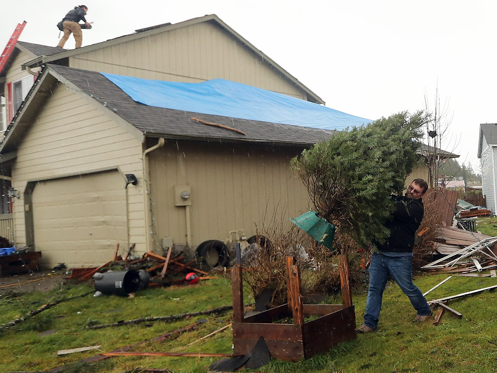John Mueller places his family's Christmas tree in the fron yard as they salvage what they can from their heavily damaged home in Port Orchard on Wednesday, December 19, 2018.