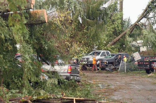 Residents and work crews clean up the aftermath of Tuesday's tornado on Serenade Way in Port Orchard on Thursday.