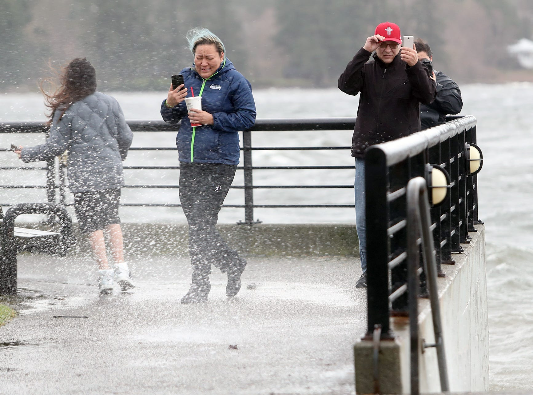 Menia Anslem, center, of Port Orchard gets battered with wind wave spray at the Silverdale Waterfront Park on Thursday, December, 20, 2018. Her daughter Jaqulyn, left, 12, dodges as her  husband Lee, right, holds onto his cap.