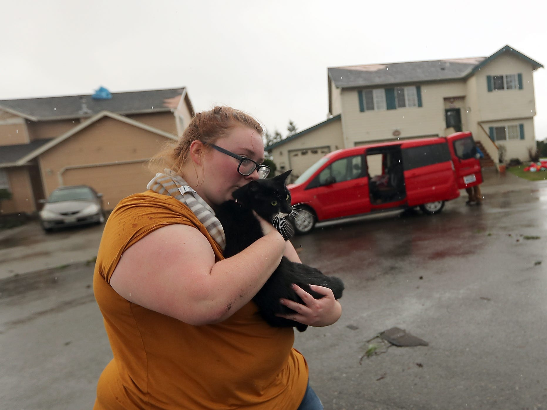 Morgan Crain snuggles her cat Loki as she rushes him from her home after finding him under a bed on Wednesday, December 19, 2018.