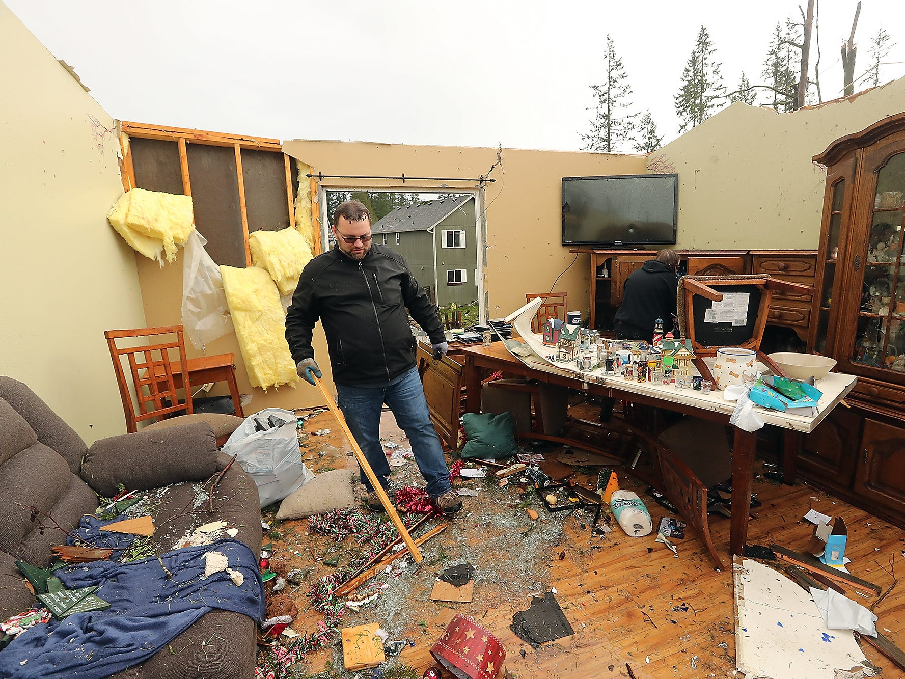 John Mueller moves through the living room of his now roofless house as he and his family try to salvage what they can from their home on Tiburon Court in Port Orchard, Washington on Wednesday, December 19, 2018. A tornado touched down in the area on Tuesday.