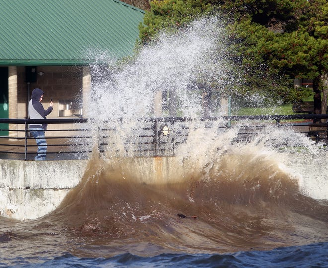 Eric Wilson backs away as a wave hits the wall at Silverdale Waterfront Park on Thursday, December, 20, 2018.
