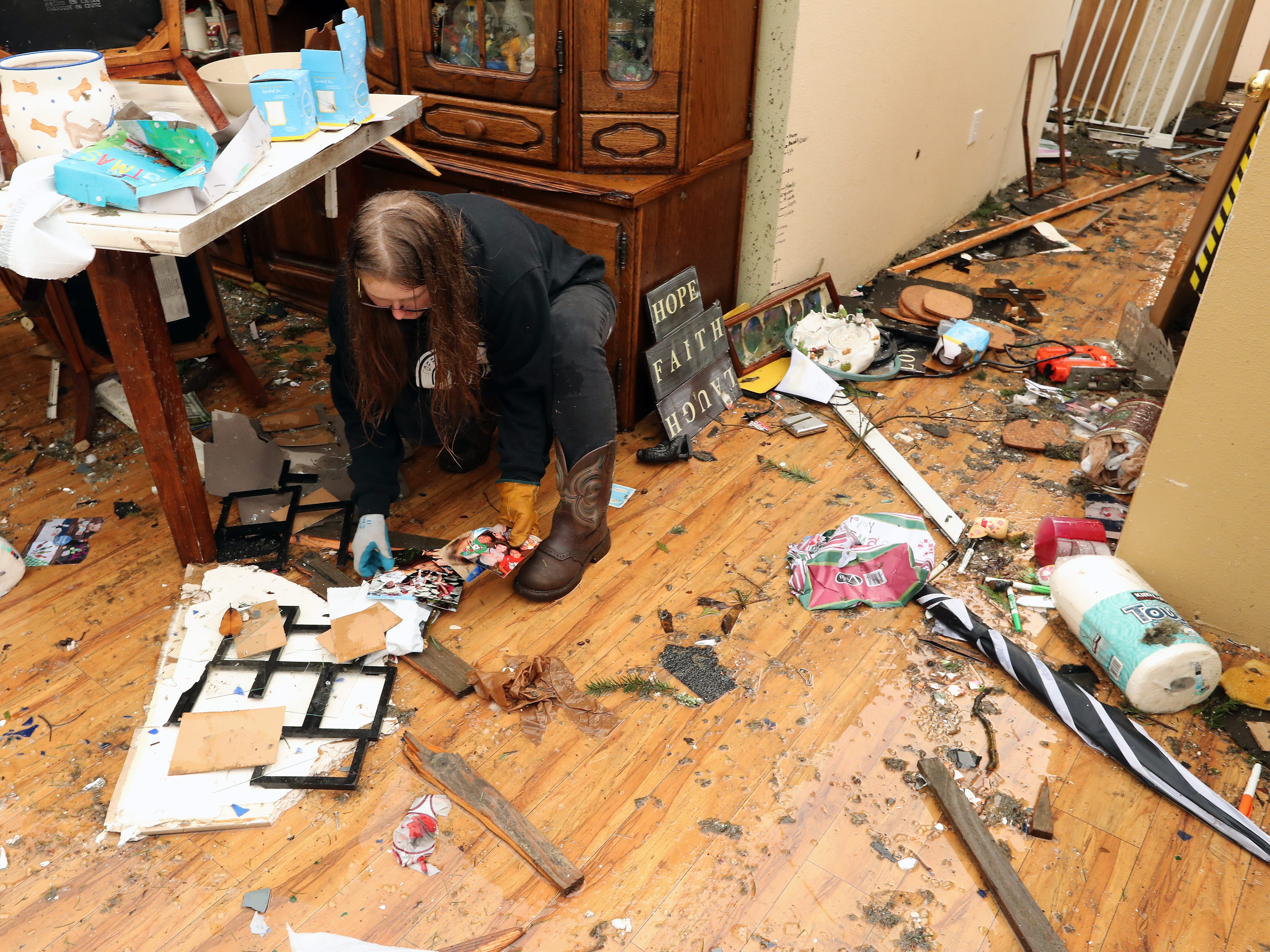 Hannah Mueller tries to salvage photos from her parents' home in Port Orchard, Washington on Wednesday, December 19, 2018. A tornado touched down in the area on Tuesday.