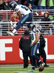 Seahawks wide receiver Doug Baldwin, bottom, celebrates with David Moore after scoring against the San Francisco 49ers on Sunday.