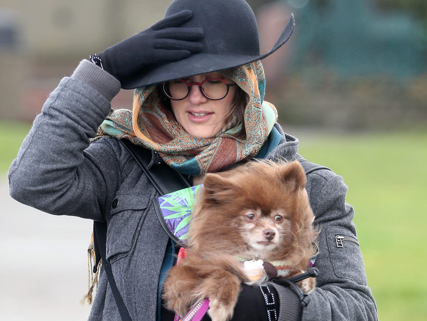 Svetlana Skalican of Kingston holds her dog Nola as she holds her hat in the wind at Mike Wallace Park in Kingston on Thursday, December, 20, 2018.