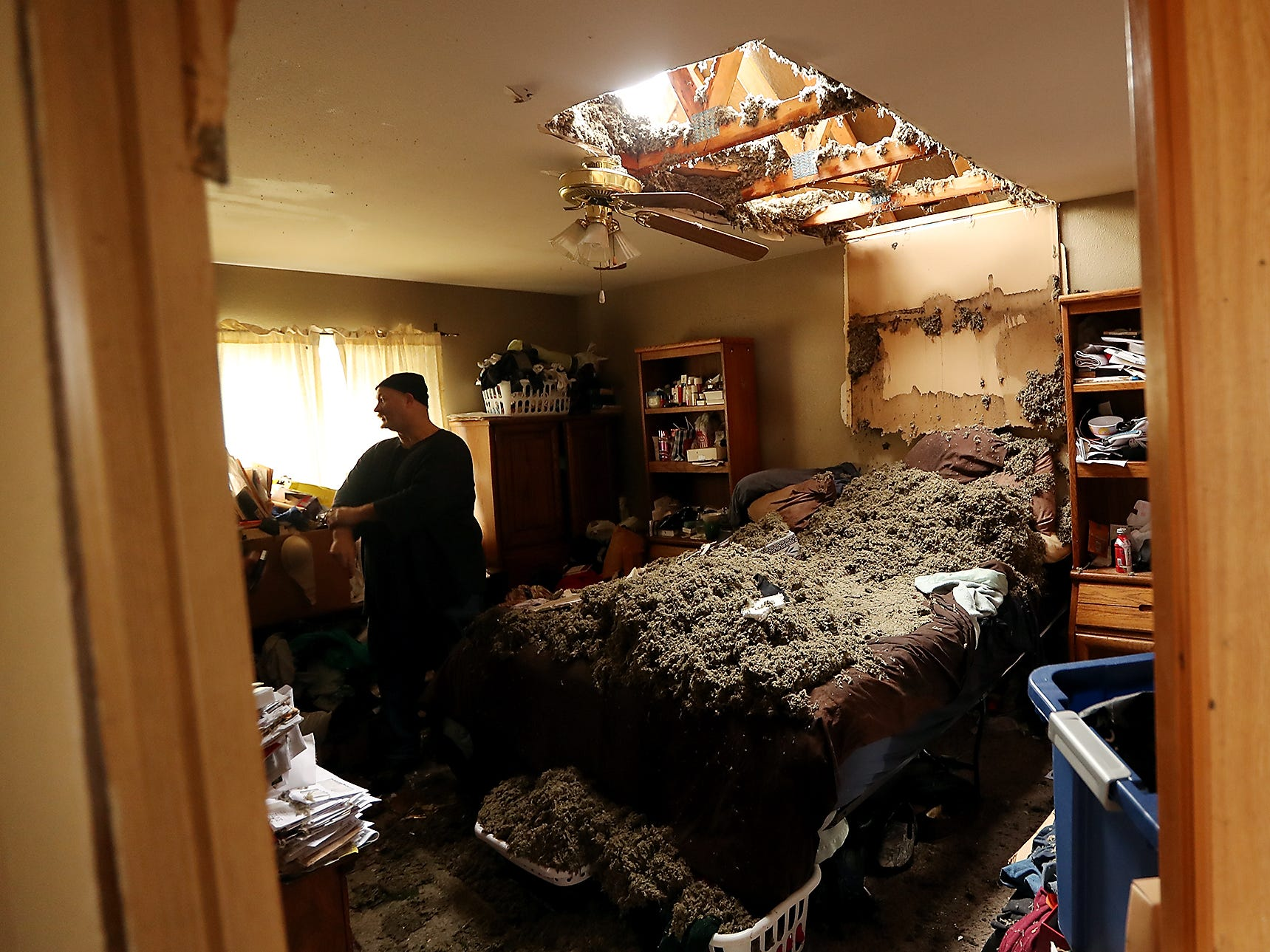 A hole in the ceiling illuminates what remains of Aaron Crain and his wife Tawnia's bedroom in Port Orchard on Wednesday, December 19, 2018.
