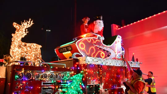 Santa and Mrs. Claus climb on Pumper 56 decked out with lights and a sleigh at the Indian Harbour Beach Volunteer Fire Station ready to head out.