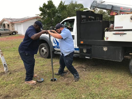 Melbourne water distribution crew leader Roy Jones (left) and maintenance technician Phillip Cote repair a damaged fire hydrant Thursday afternoon on Magnolia Avenue.