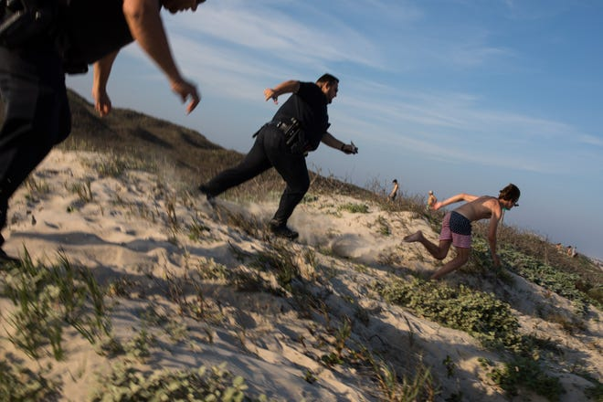 A spring breaker runs from police officers Joseph Rivas and Gabriel Lopez before bring giving a warning for having glass on the beach in Port Aransas during the first day of spring break on Saturday, March 10, 2018.