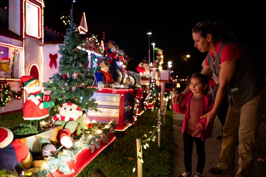 Marie Pricott and 5-year-old Angelica look a the displays at Mr. Bill's Christmas home on Hampton Street on Wednesday, Dec. 19, 2018. For 20 years Mr. Bill has decorated his home with an elaborate display of Christmas decorations.