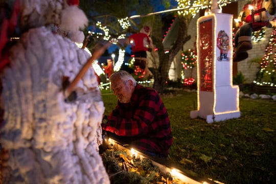 Mr. Bill works to fix an animatronic snowman in front  of his home on Hampton Street on Wednesday, Dec. 19, 2018. For 20 years Mr. Bill has decorated his home with an elaborate display of Christmas decorations.