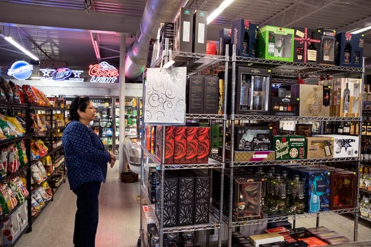Sandy Coleman, a personal shopper, shops for Christmas gifts, at Liquid Town on South Alameda Street on Thursday, December 20, 2018. The store will be closed due to state law on Christmas Day and New Year's Day.