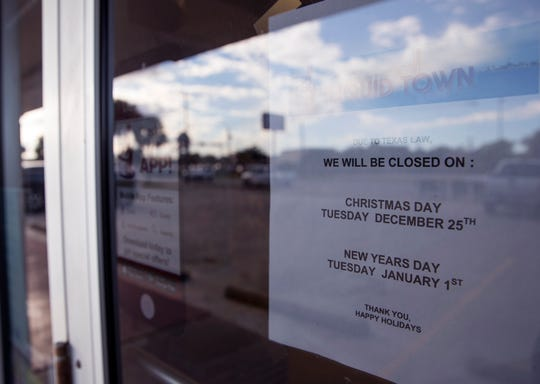 A sign on the door at Liquid Town on South Alameda Street reminds shoppers that the store will be closed due to state law on Christmas Day and New Year's Day.