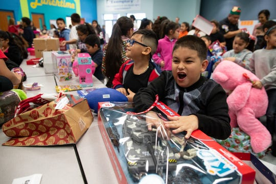 Third grade students open presents at Shaw Elementary from Santa and Corpus Christi Independent School District police officers handed them out on Thursday, Dec. 20, 2018.