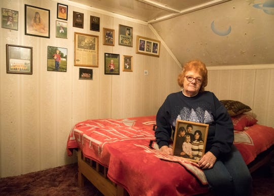 Surrounded by Ohio State memorabilia and pictures keepsakes, Donna Keller cradles one of her favorite pictures of her and her children as she sits in the bedroom that once housed her sons and daughter,