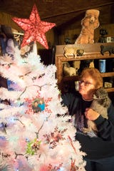 Clutching her poodle Emmy for support, Donna Keller looks at different photo ornaments, each with a story behind almost everyone, that she placed on the Memory Tree that she created to honor the lives of her sons Gary Darling Jr. and Shawn Darling Sr. She lost both sons within a year's time to a rare genetic disorder called Huntington's disease.