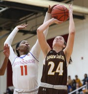 Purcell Marian guard Kya Dukes (11) blocks a shot by Roger Bacon guard Kelly Brenner.