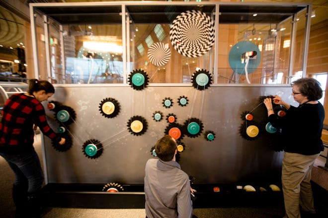 People play with the gears of a ball drop contraption at the Museum of Natural Science and History on Thursday, Dec. 20, 2018, in the Cincinnati Museum Center at Union Terminal, Cincinnati.