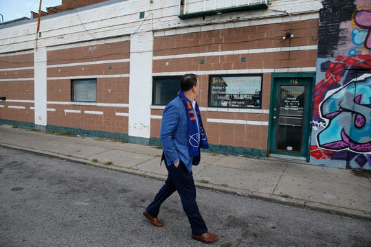 Jeff Berding walks past Just Cookin Catering on West 15th Street in the West End Friday October 19, 2018.The resturant will be torn down to make room for the new FC Cincinnati Stadium.