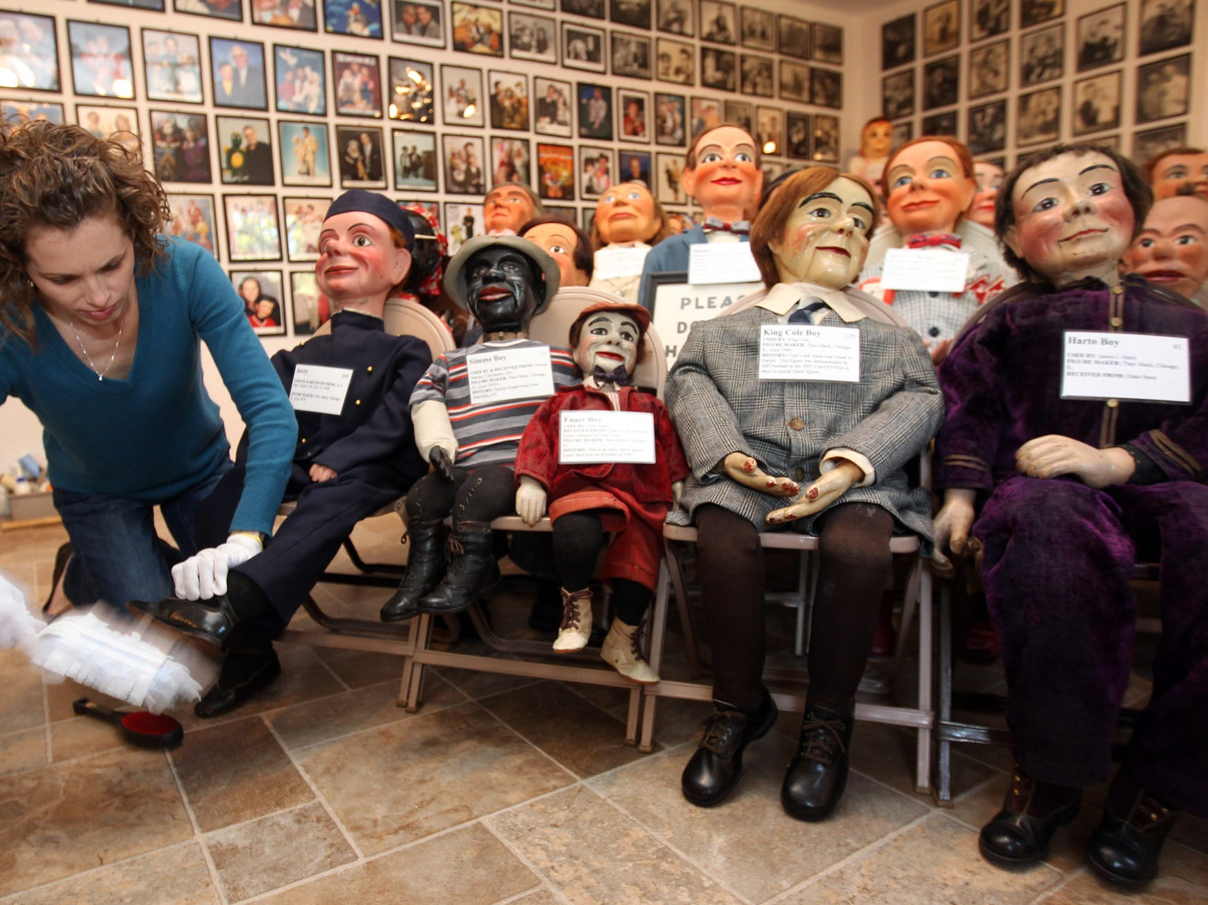 Jen Dawson, curator of the Vent Haven Museum, dusts the shoes of one of the more than 800 figures at the world's only museum dedicated to the art of ventriloquism.