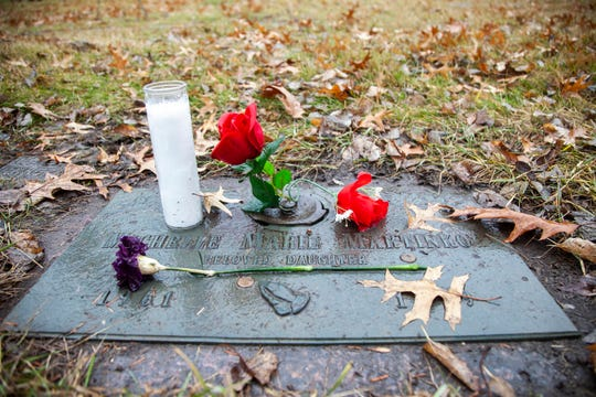 A carnation and two roses sit next to a white candle on Michelle Marie Martinko's grave on Thursday, Dec. 20, 2018, at the Cedar Memorial Park Cemetery in Cedar Rapids.