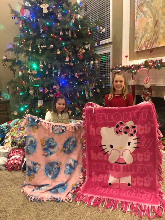 Nora Huebsch, 7, and sister Charlotte Huebsch, 10, hold the blankets they received when their sister, Lucy, was stillborn in 2013. The family went on to create a charity that donates hundreds of blankets to sick children and their families on Christmas each year.