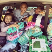 The Huebsch family of Ankeny packs their car with fabric to be made into fleece blankets for sick children.
