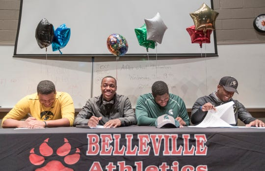 Julian Barnett, second from left, and Devontae Dobbs, third from left, sign with Michigan State at Belleville High Schoo on Wednesday.