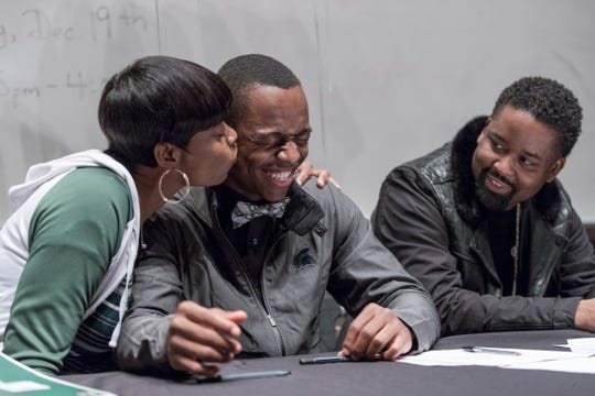 Daun Barnett kisses her son Julian Barnett, after he signed his letter of intent to play for Michigan State University at Belleville High School, Wednesday, Dec. 19, 2018. Next to them is Julian's cousin, Jamal Barnett.