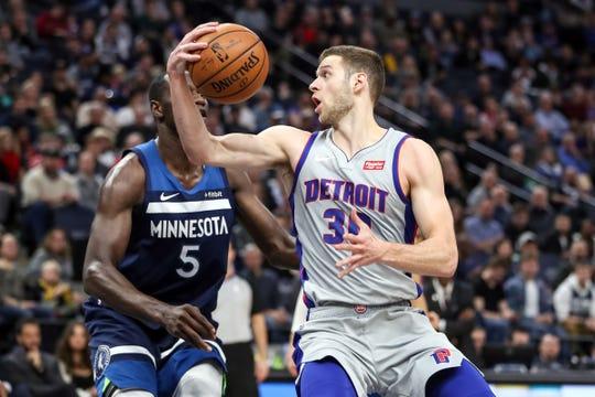 Detroit Pistons forward Jon Leuer drives past Minnesota Timberwolves center Gorgui Dieng during the second quarter at Target Center, Dec. 19, 2018.
