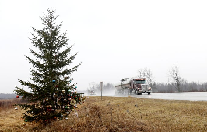 Traffic passes a pine tree on I-75 near mile marker 199 in Moffatt Township, Michigan on Friday, Dec. 20, 2018. The tree was planted at the spot where Jason Porter was killed 20 years ago by a drunk driver, but strangers have turned it into a Christmas tree over the years.