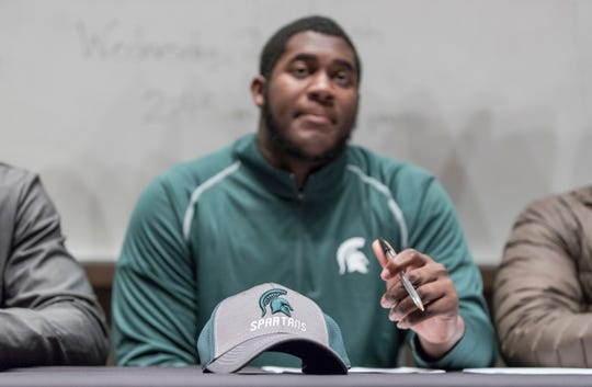 Devontae Dobbs looks up as he gets ready to sign his letter of intent to play for Michigan State University at Belleville High School, Wednesday, Dec. 19, 2018.