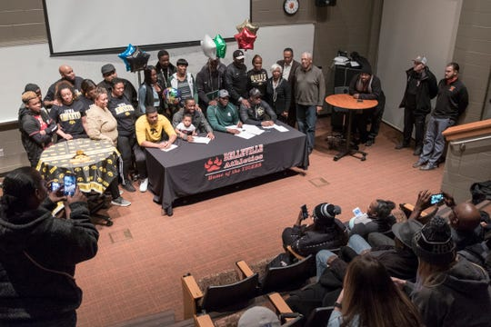 From left, Jalen Hunt signs with Iowa, Julian Barnett and Devontae Dobbs sign with Michigan State and Marvin Ham signs with Colorado at Belleville High School, Wednesday, Dec. 19, 2018.