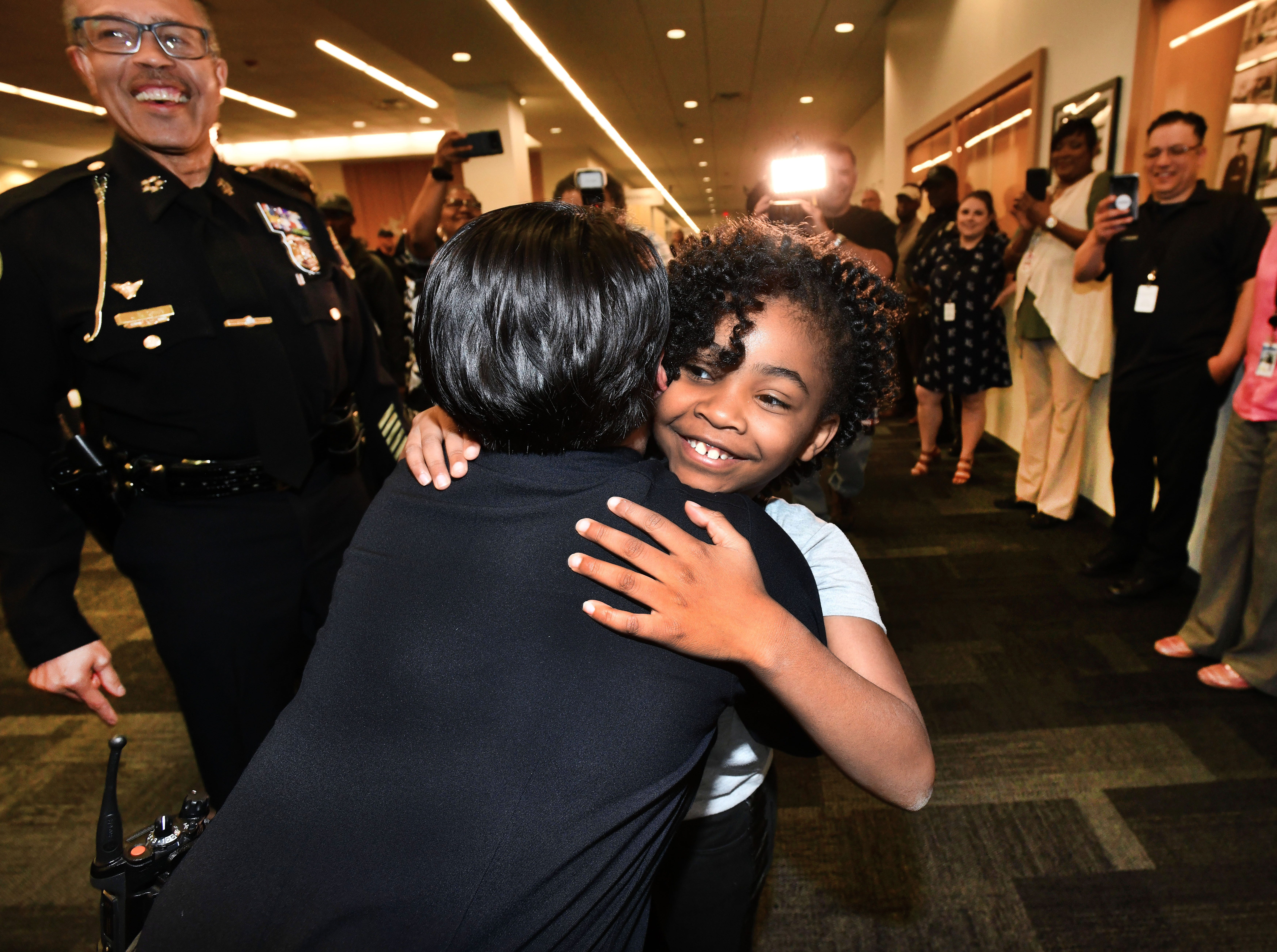 Cpl. Renee Stanley gets a hug from Rosalyn Baldwin as Police Chief James Craig and other officers at Detroit Police headquarters got a wonderful surprise from the inspirational 8-year old. After five Dallas police officers were killed in 2016,  8-year old Rosalyn Baldwin decided that she would go across the country and hug police officers. She stopped in Detroit on May 14, 2018.