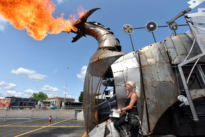 """""""Heavy Meta"""" creative director Marie Poliak, 30, of Toronto, remotely operates the fire-breathing dragon on Canada's largest art car, at the Henry Ford Maker Faire Detroit in Dearborn, July 28, 2018.  The dragon is built over a GMC Minibus and will be completely disassembled and placed in a trailer as Heavy Meta travels to their next show location."""