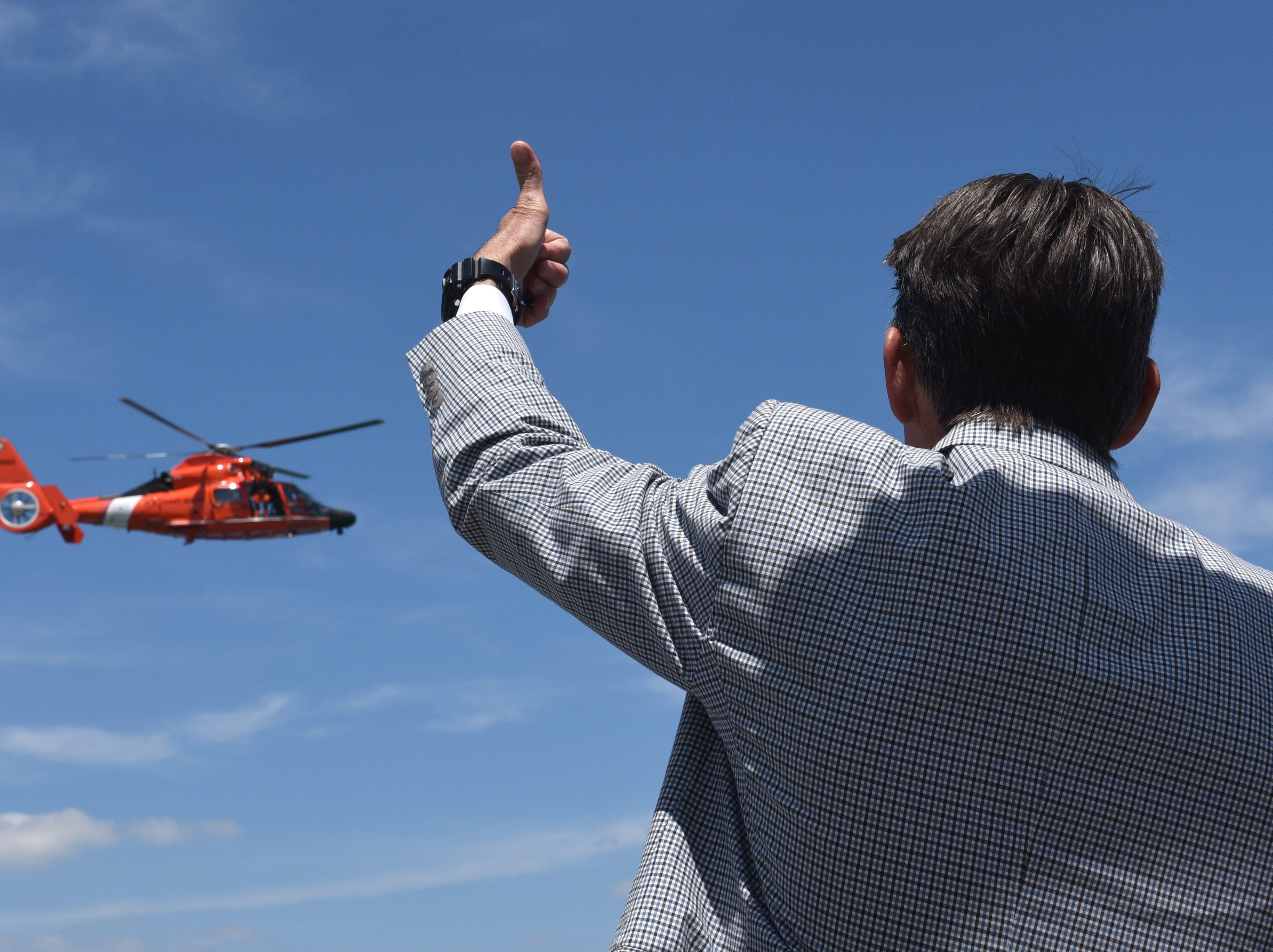 Mark Hackel, Macomb County executive, gives a thumbs up to a  U.S. Coast Guard helicopter that performed a live rescue at the MacRay Harbor Marina in Harrison Township on June 6, 2018. Hackel, spoke along the shore of Lake St. Clair to share accomplishments, advancements and work around the regionÕs land and water resources.