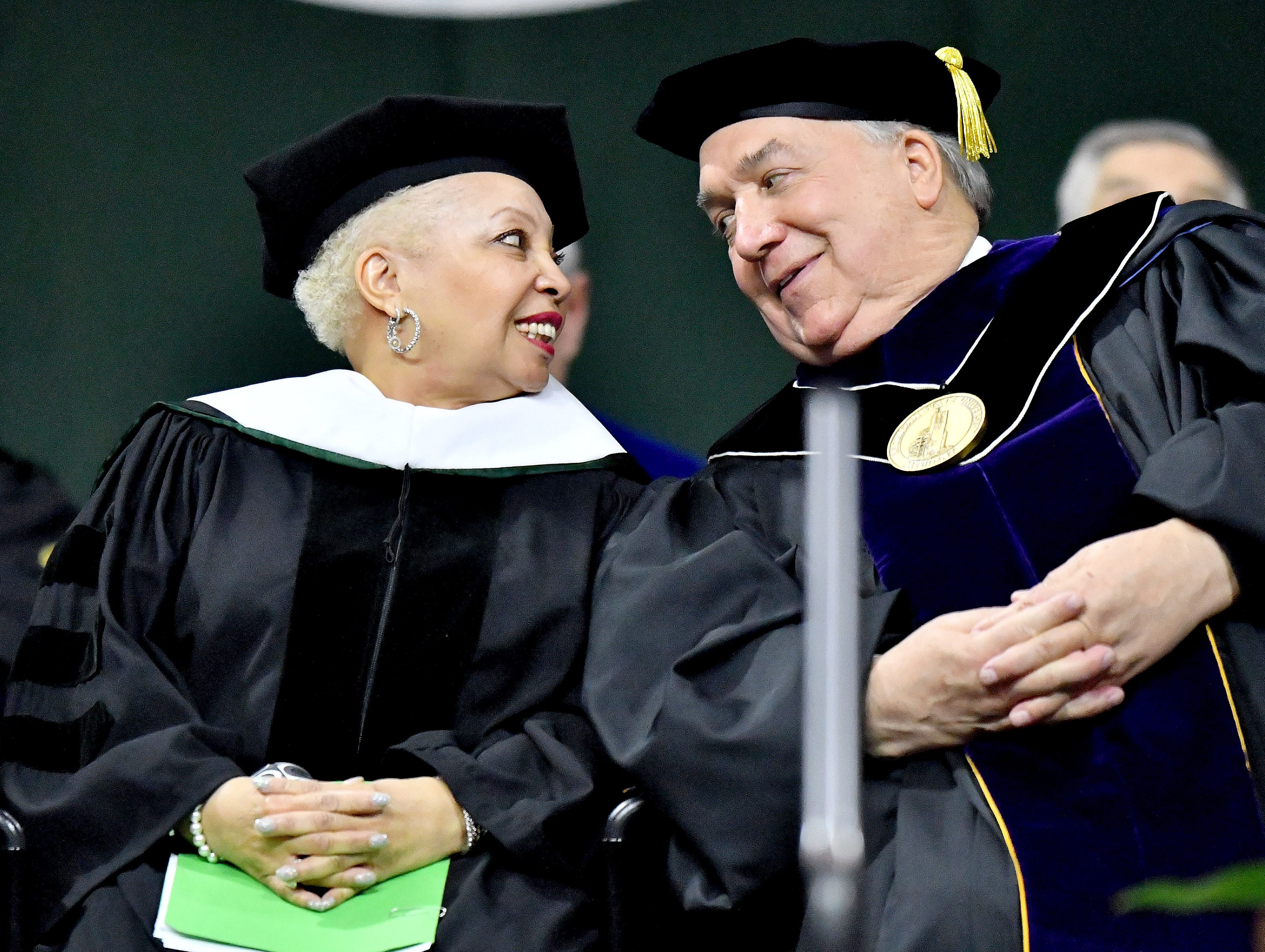 Former Starbucks executive Wanda Herndon shares a chuckle with interim President John Engler at the Michigan State University commencement ceremony on May 4, 2018 in East Lansing.