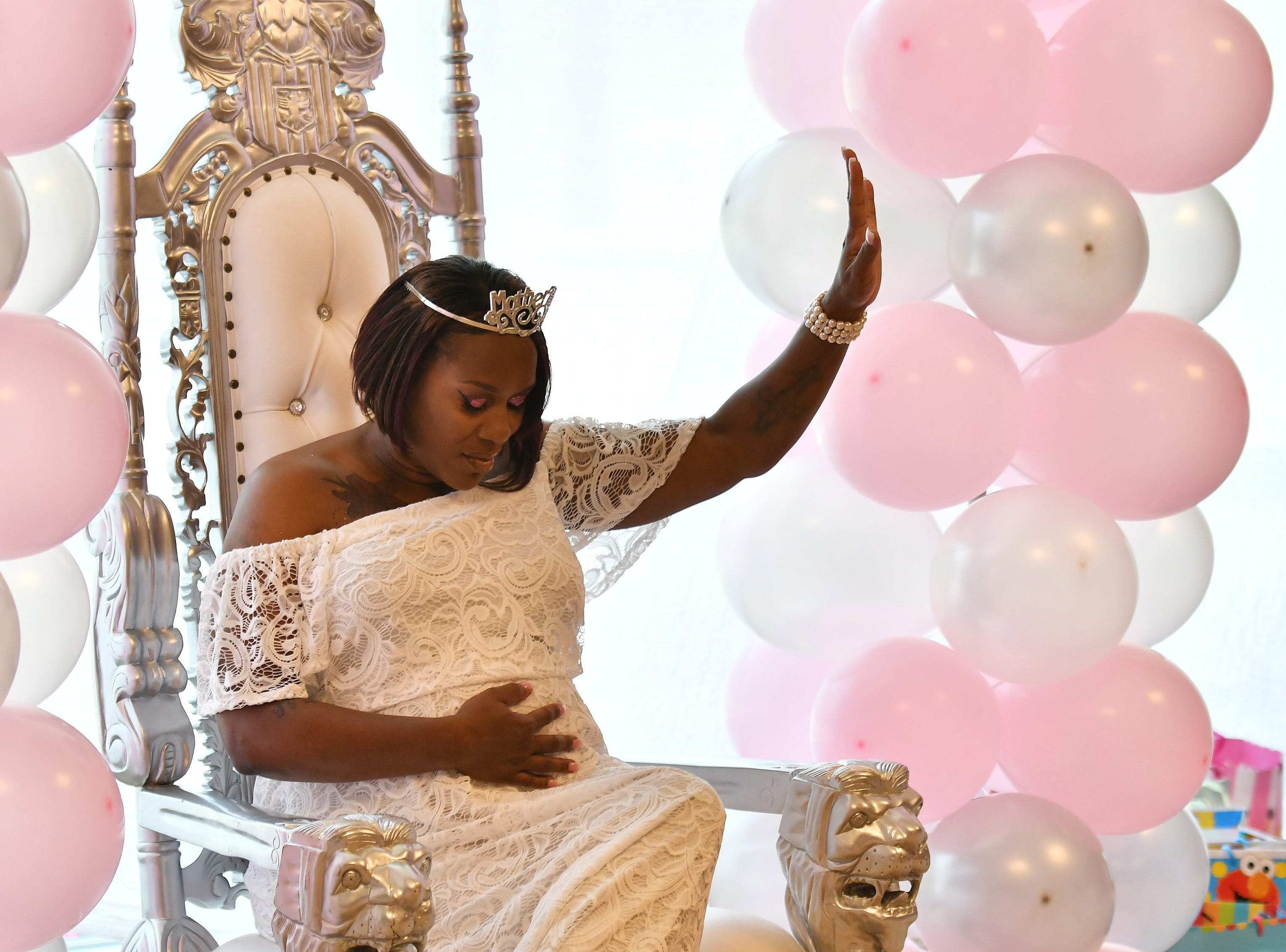 Kim Simmons raises her hand and feels her belly while a prayer is said at a community baby shower for her at Horatio Williams Foundation in Detroit on July 15, 2018. Simmons is one of two female juvenile lifers who was released from prison last year. While in prison she dreamed of having a baby and being able to raise it. Now her dream is coming true.