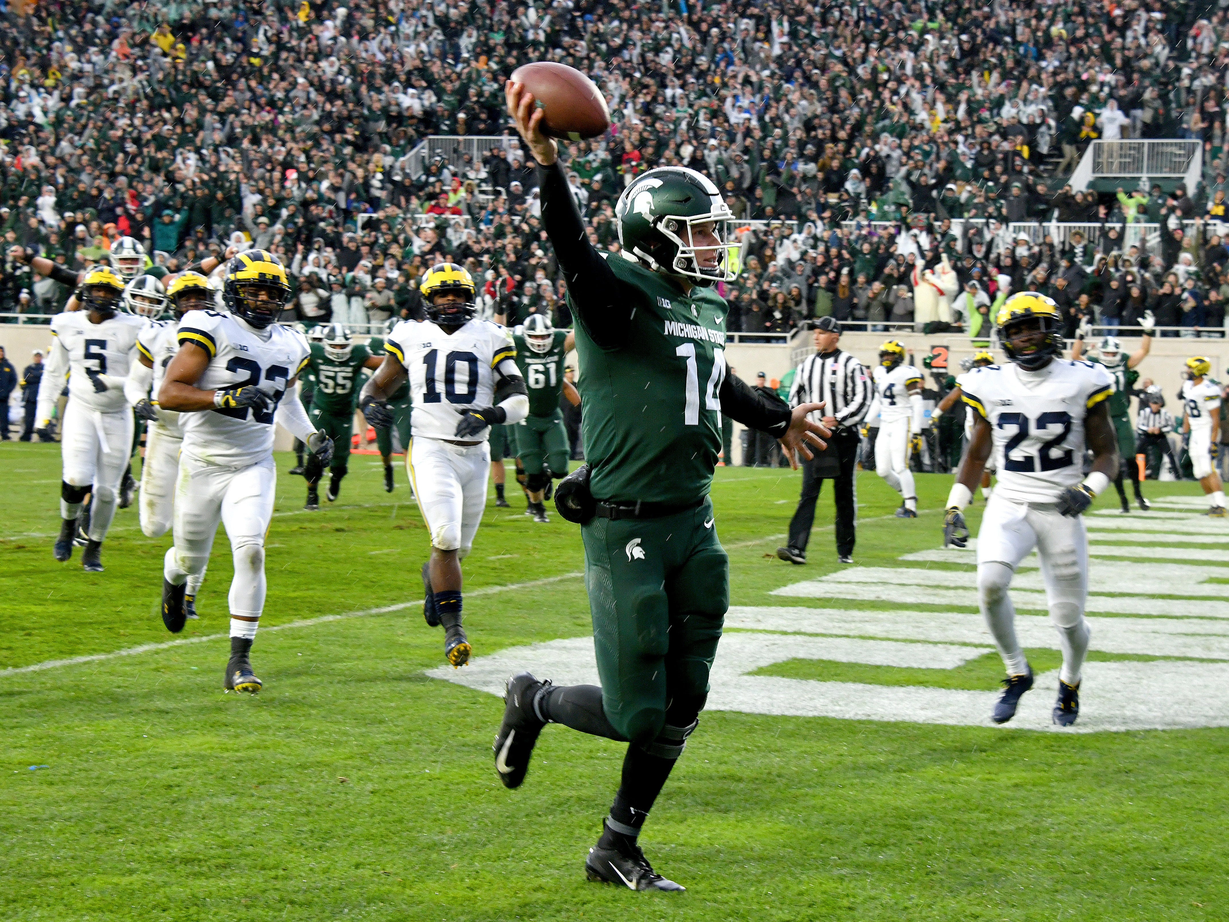 In one of the few Spartans bright moments, MSU quarterback Brian Lewerke holds the ball aloft after catching a touchdown pass in the third quarter against Michigan. The Wolverines had the last laugh, however, reclaiming the Paul Bunyan trophy with a 21-7 victory at Spartan Stadium on Saturday, Oct 20, 2018.