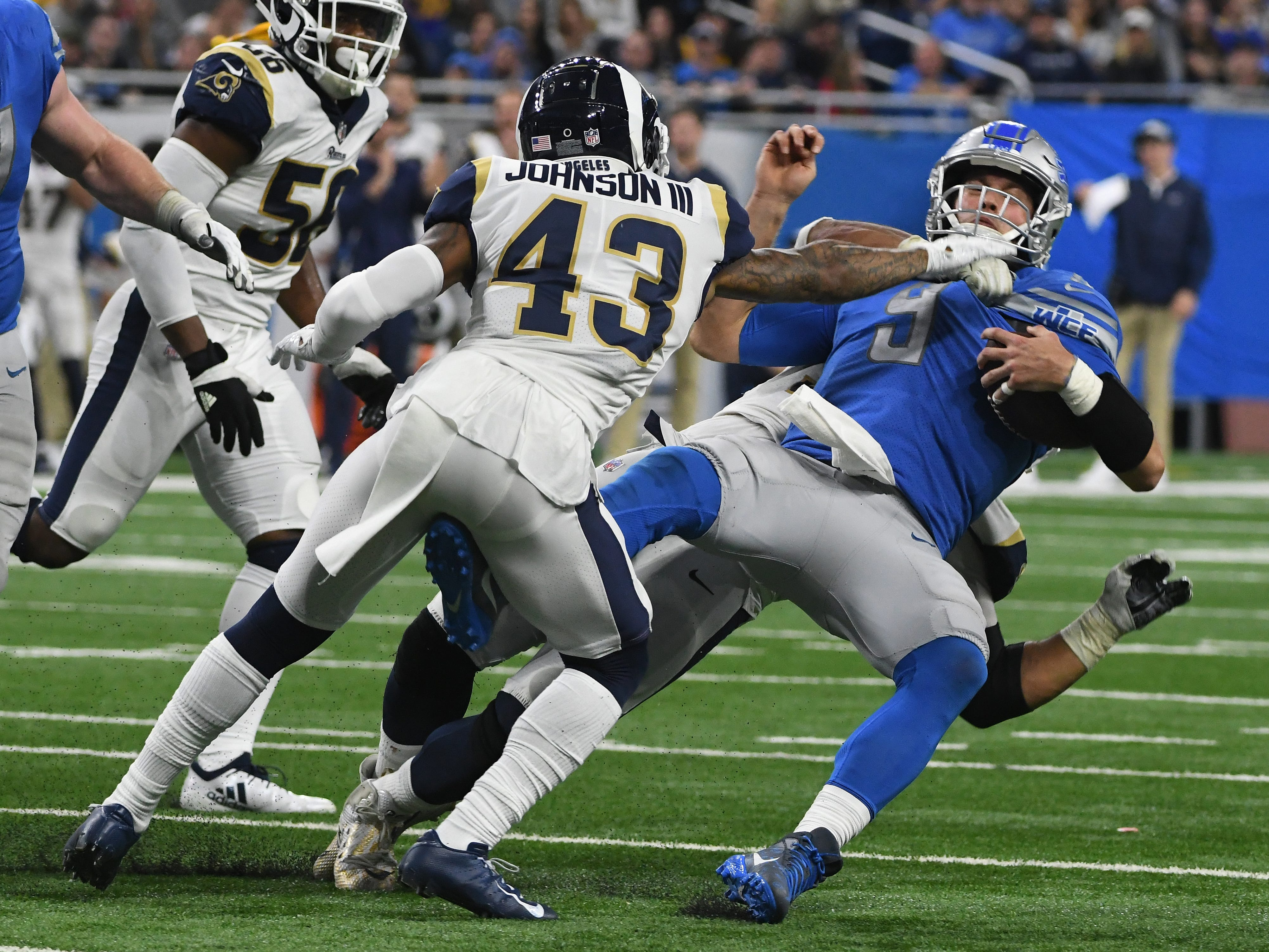Lions' Matthew Stafford is sacked by Rams' Ethan Westbrooks and John Johnson III, but off-setting penalties, forced both teams to replay the down during a 30-16 loss at Ford Field in Detroit, Michigan on December 2, 2018.