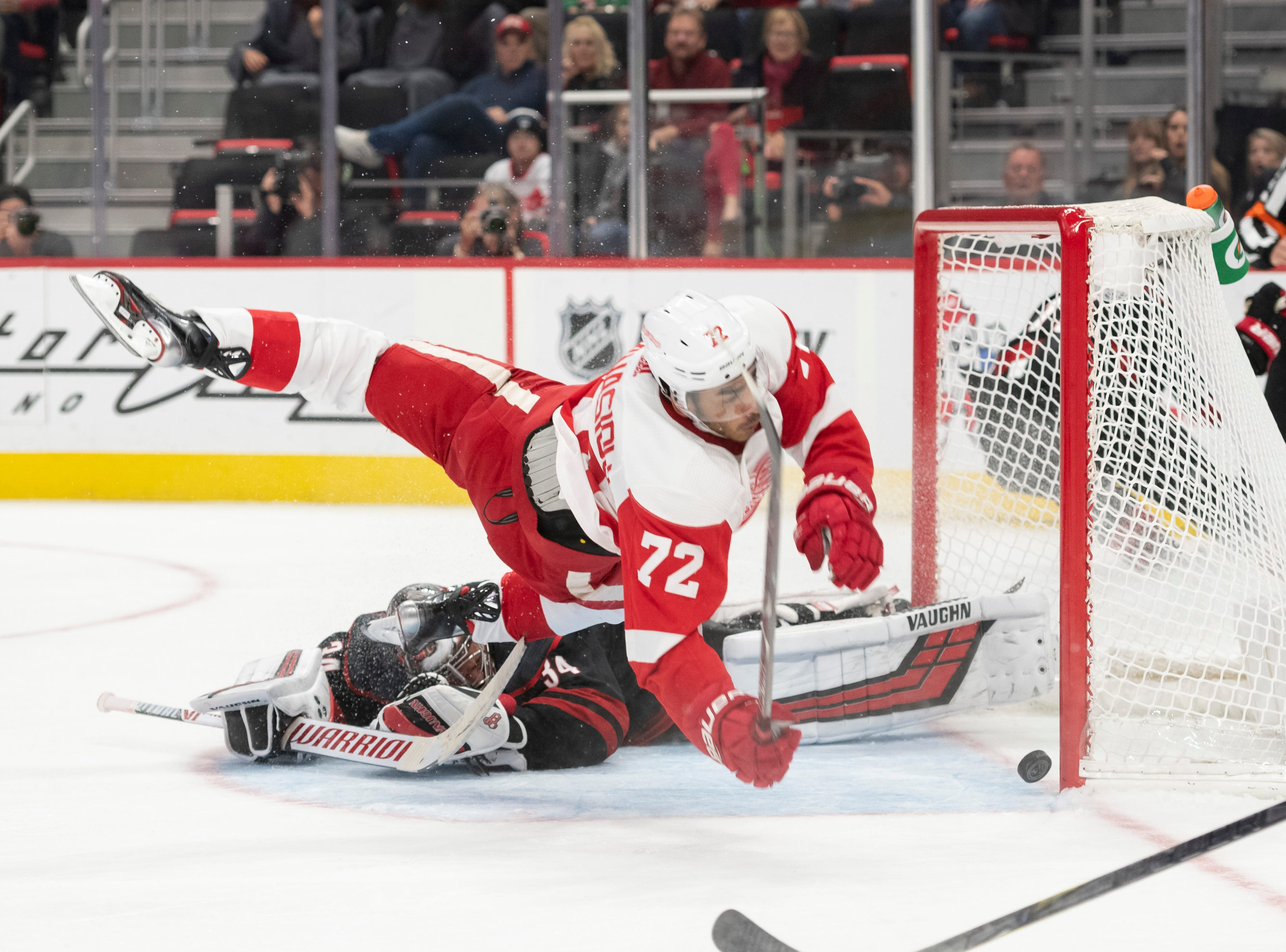 Detroit center Andreas Athanasiou collides with Carolina goaltender Petr Mrazek as he scores a goal in the third period at Little Caesars Arena, in Detroit, October 22, 2018.  Detroit lost 3-1.