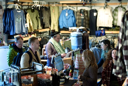 Jake Fleming of Detroit, second from left, buys gift cards for his family gift exchange as Moosejaw assistant manager Michaela Jajko rings up his purchase Wednesday in downtown Detroit.