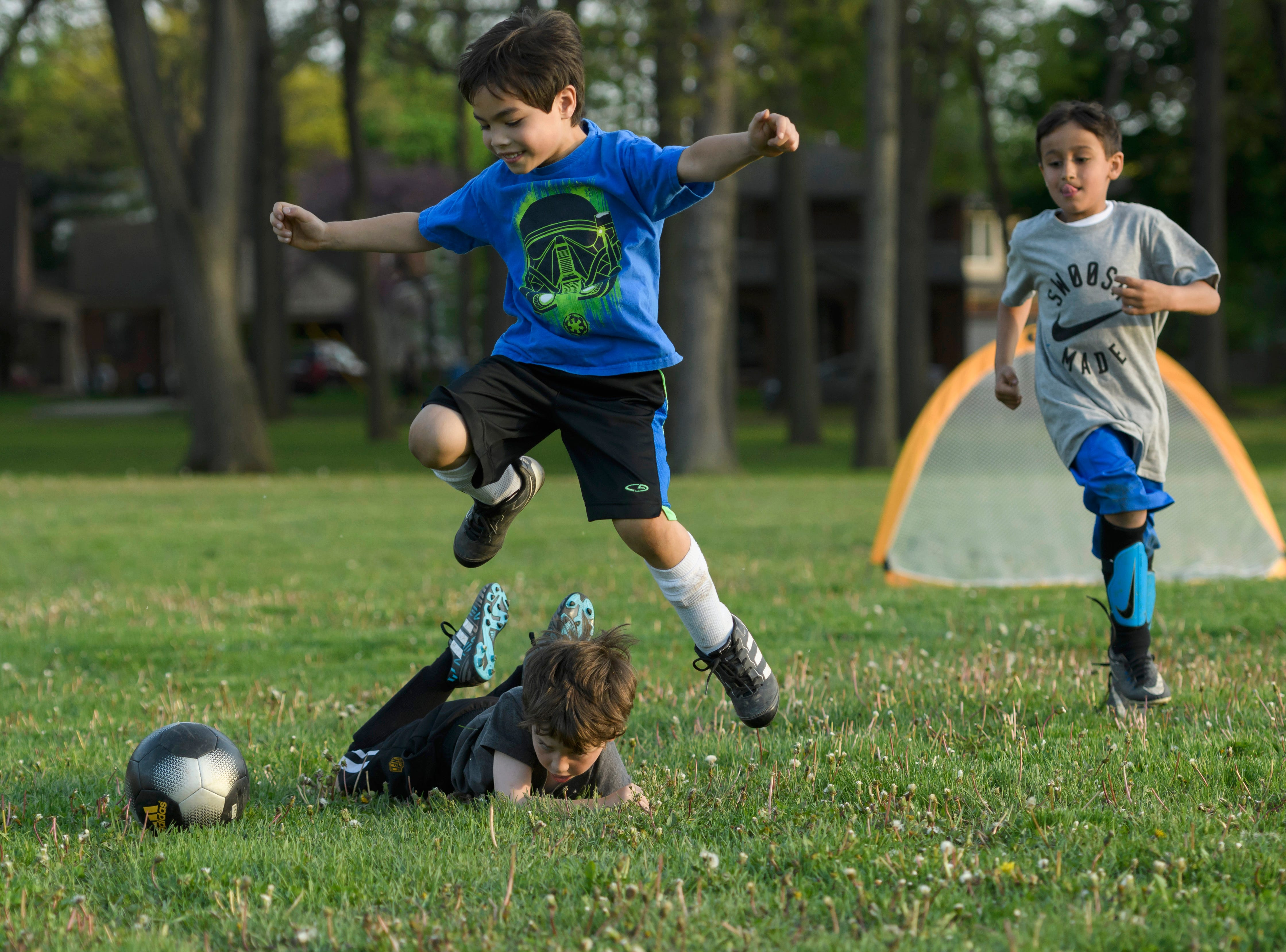 Carson Post leaps over the top of Owen Sanderson-Price while chasing after the ball during Dearborn Cougars 11 soccer team  practice at Howard Elementary School in Dearborn, May 16, 2018.