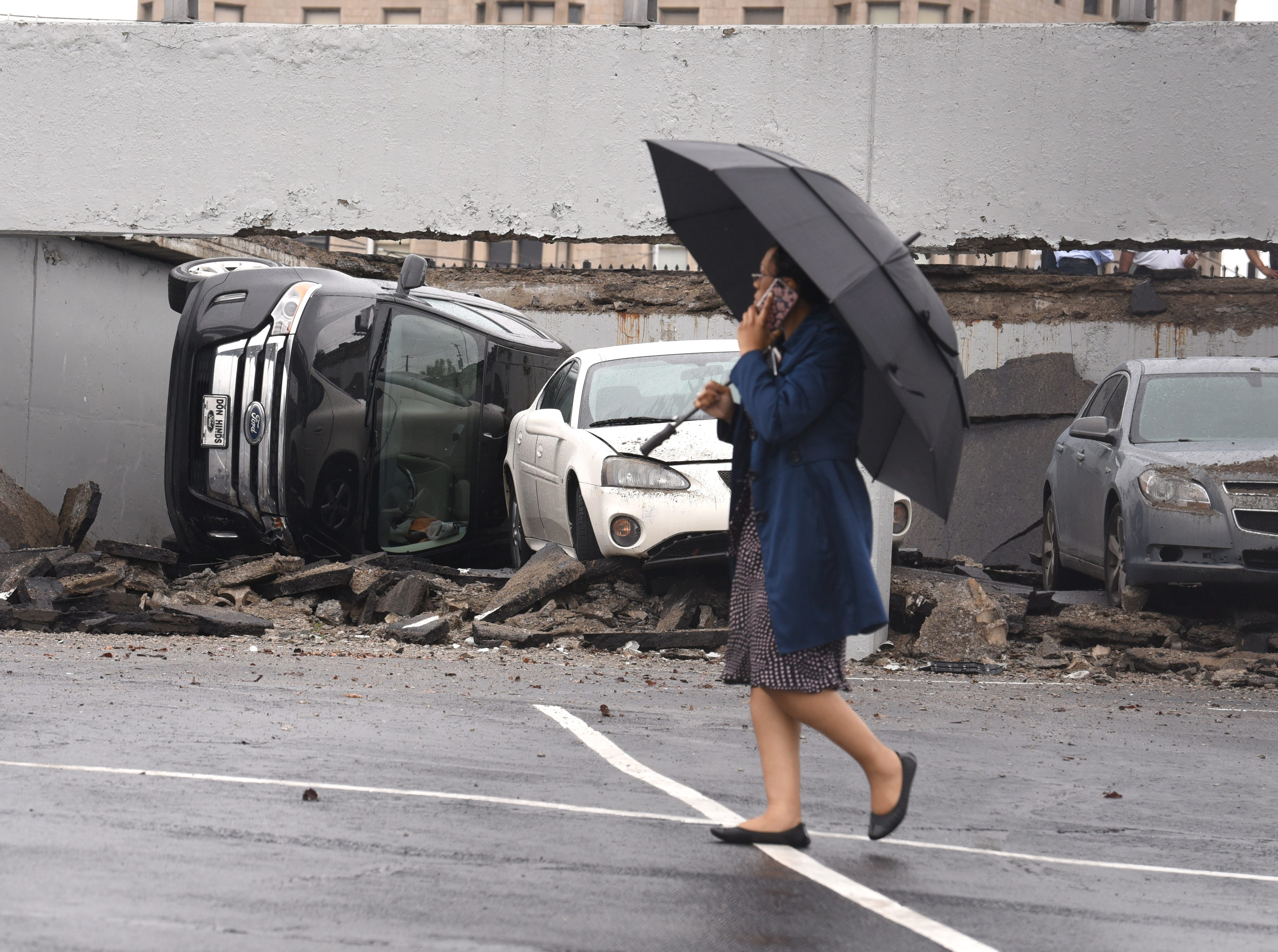 A woman walks by cars damaged by the collapse of a parking structure at Rivard and Franklin in Detroit on May 3, 2018.