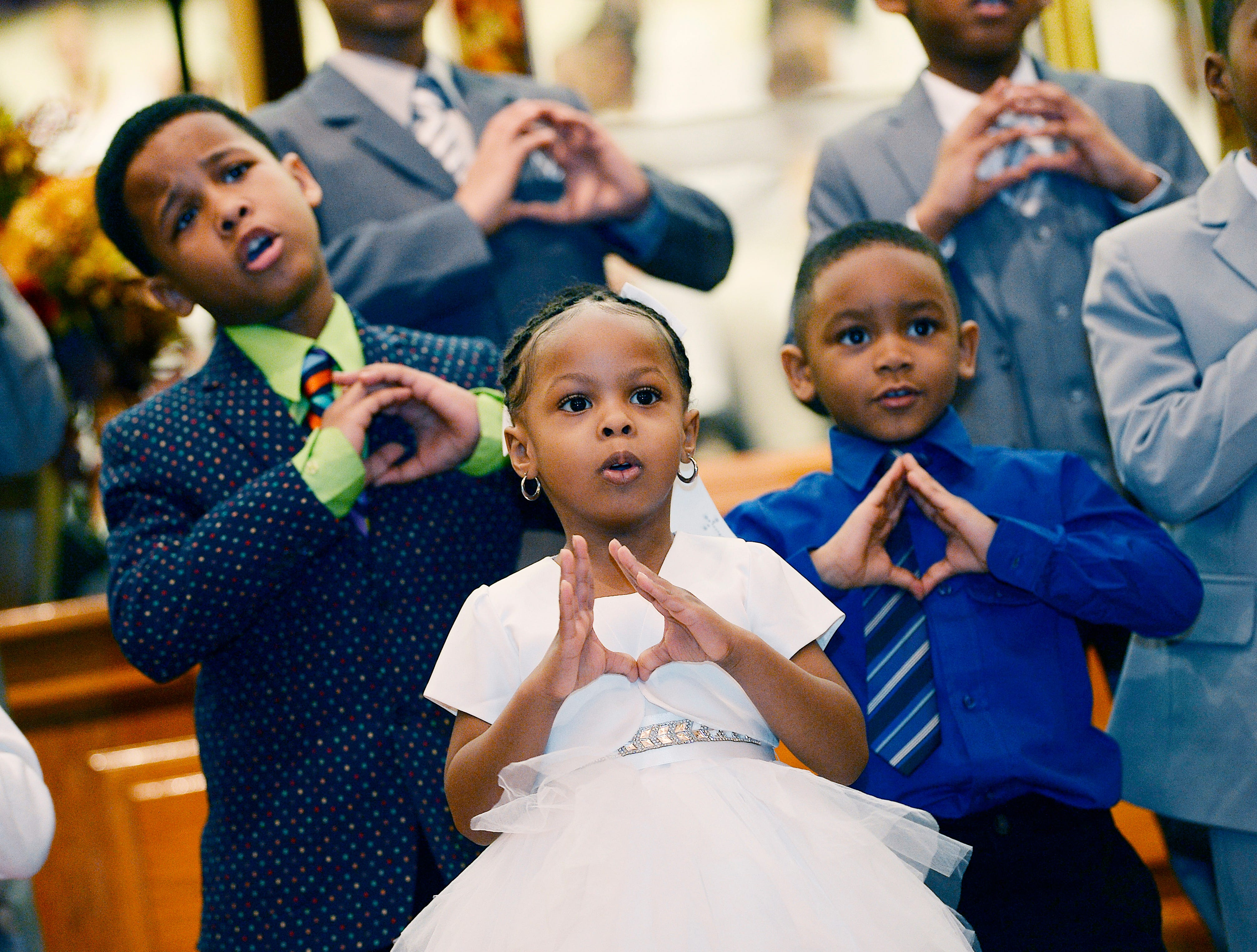 "Members of the Kidz of the Kingdom Choir, from left, Caleb Proctor, 8,  Abigail Paul, 3, and Austin Wyldon, 4,  sing  ""Bless the Lord O My Soul""  during the Easter service at Perfecting Church in Detroit on April 1, 2018"