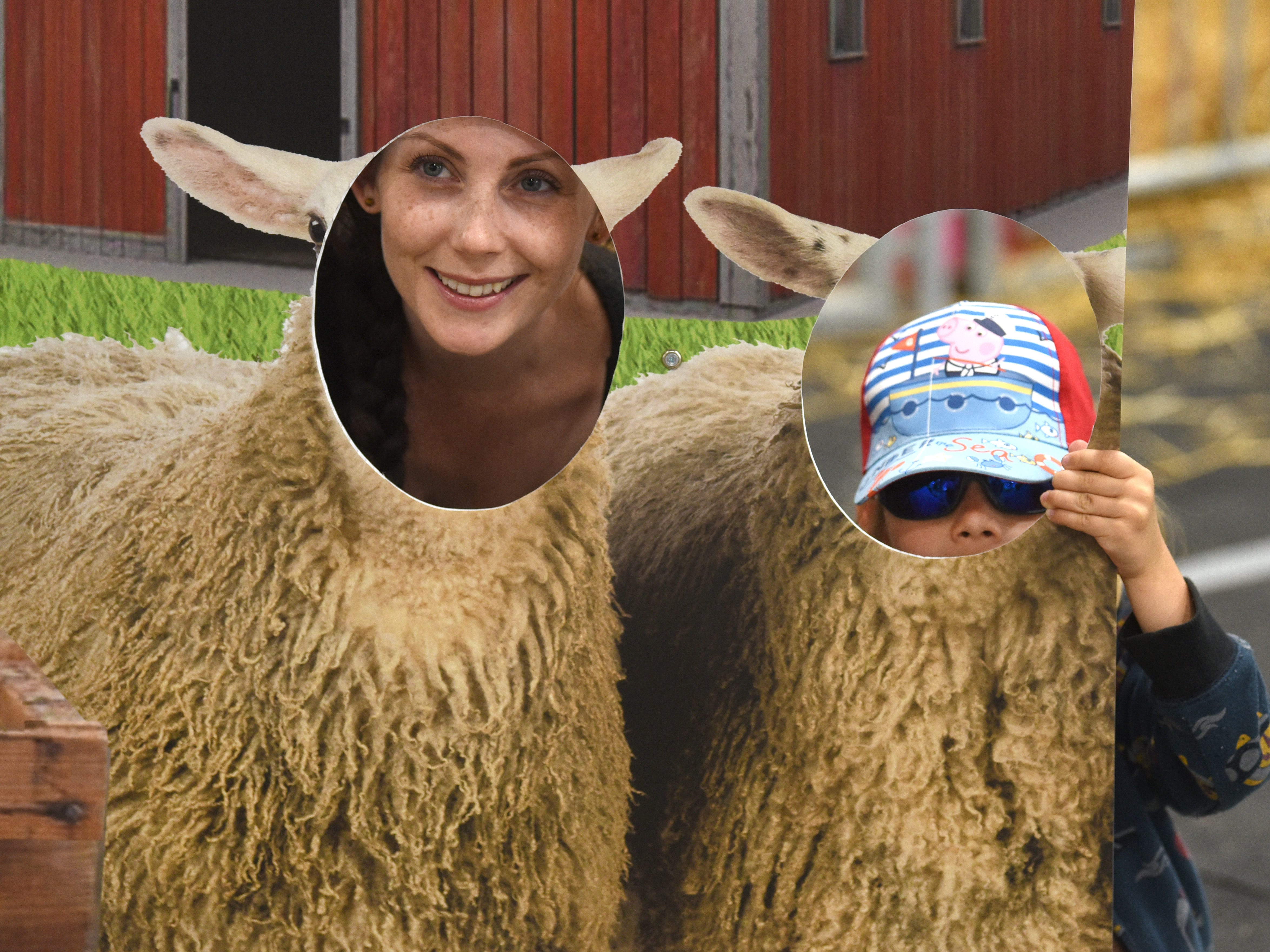 Kelly Denooyer, left, and Sebastian Pieracuoli, 3, pose as sheep in the livestock area at the Michigan State Fair at the Suburban Collection Showplace in Novi on August 30, 2018.