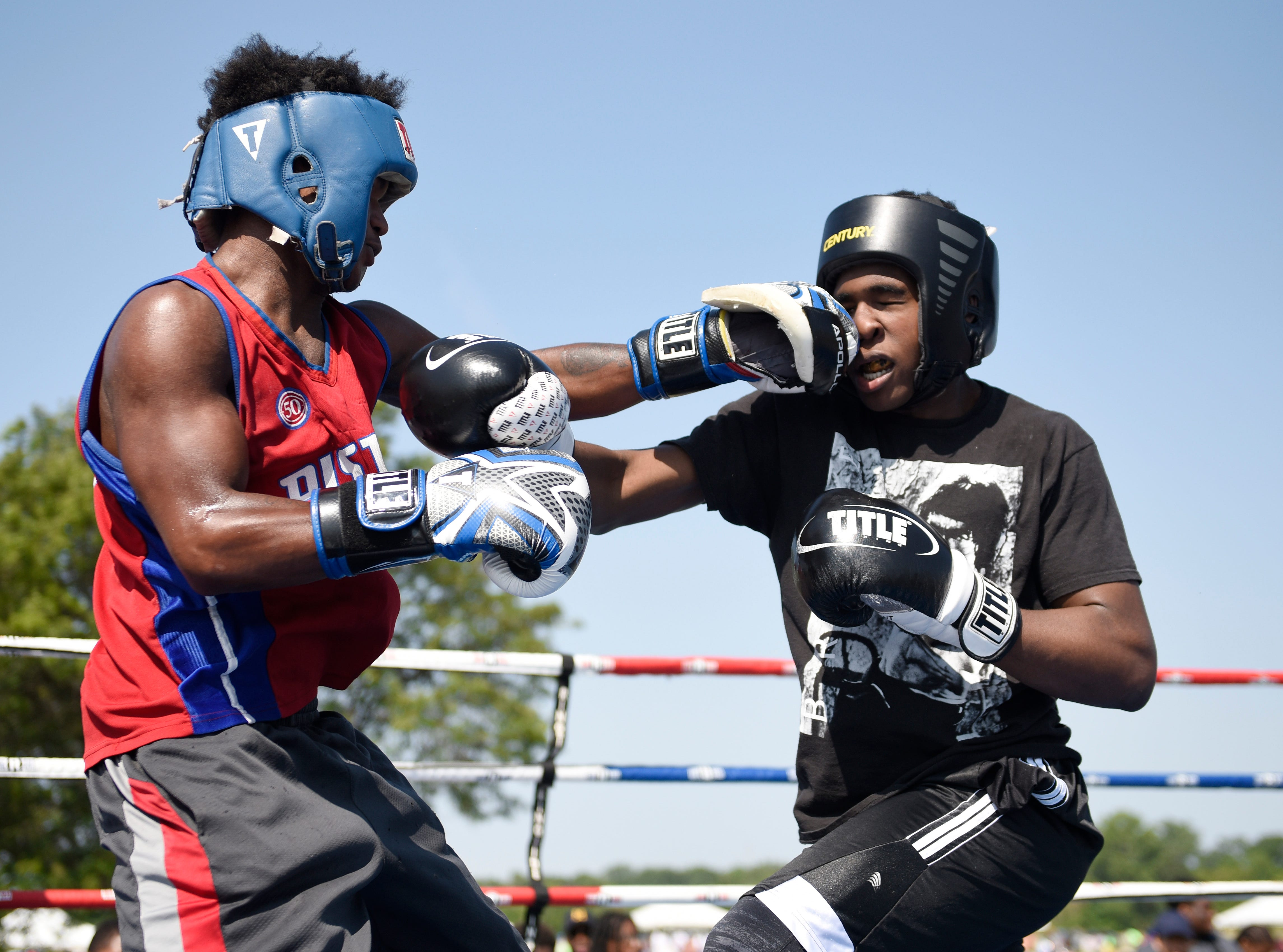 Deonte Cheeves, left, 18, and DeAndre Madison,15, both of the Jimmie Paul Hands On boxing gym, battle in the ring during a match at the 36th Annual Metro Detroit Youth Day at Belle Isle park in Detroit on July, 11, 2018.